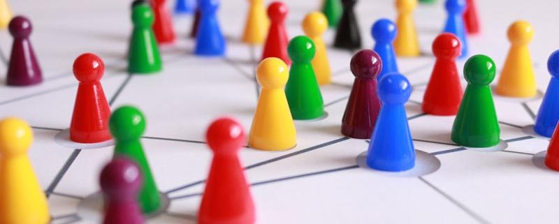 Spielfiguren auf Tisch die miteineinder vernetzt sind.